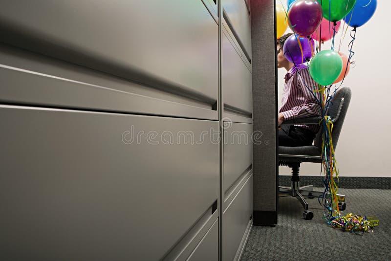 Geschäftsmann saß mit den Ballonen, die an seinem Stuhl gebunden wurden lizenzfreie stockfotografie