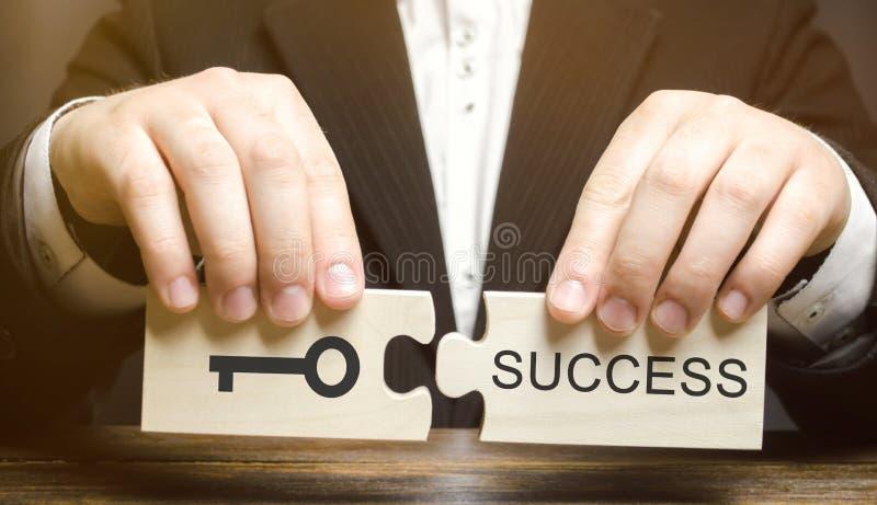 Geschäftsmann sammelt die hölzernen Puzzlespiele, die zum Erfolg Schlüssel sind Konzept des Erzielens des Ziels, Schwierigkeiten  stockfotos