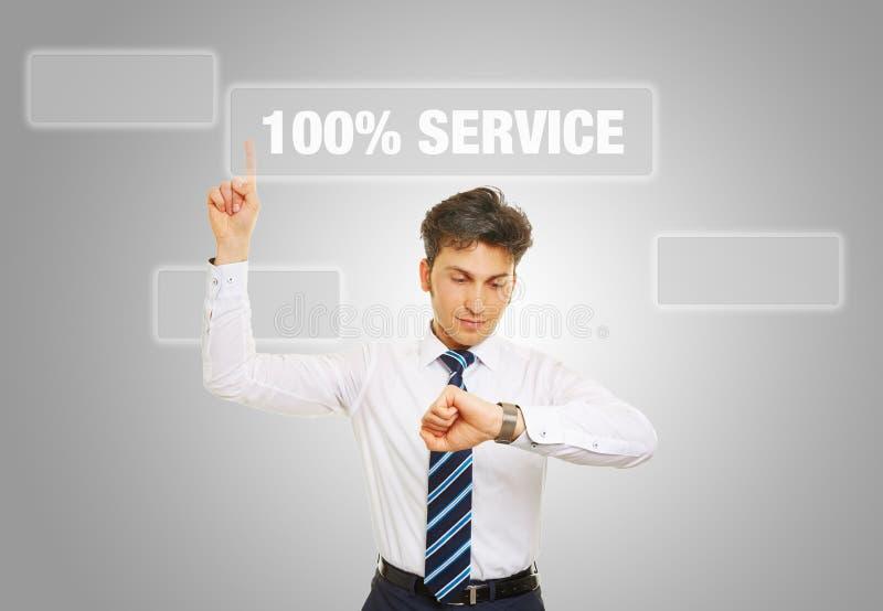 Geschäftsmann schaut auf Uhr mit Service des Slogans 100% lizenzfreie stockbilder