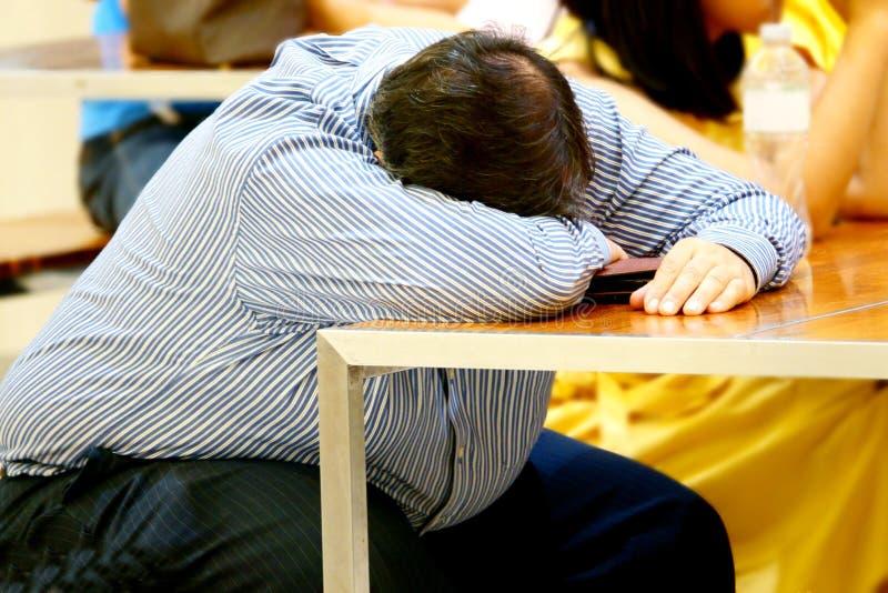 Geschäftsmann schläft auf dem Schreibtisch nach müdem überbelastet lizenzfreie stockbilder