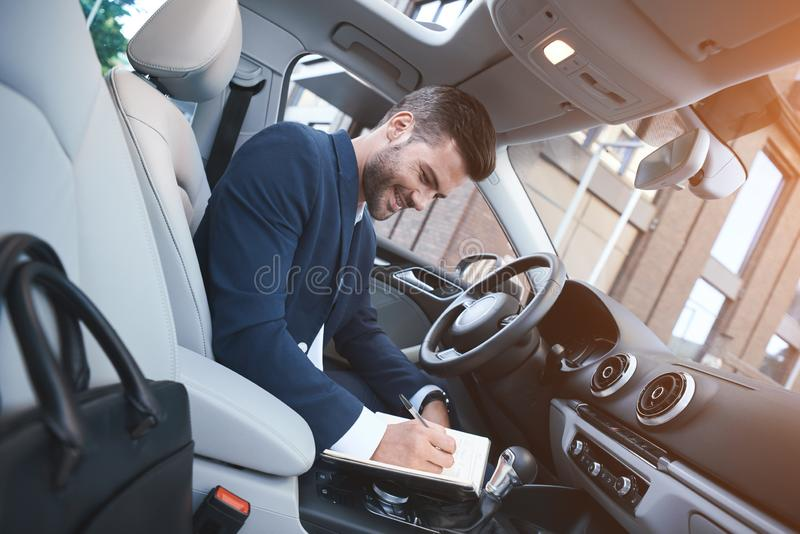 Geschäftsmann schreibt Anmerkungen in das Auto und wird zu einer Sitzung fertig lizenzfreie stockfotografie