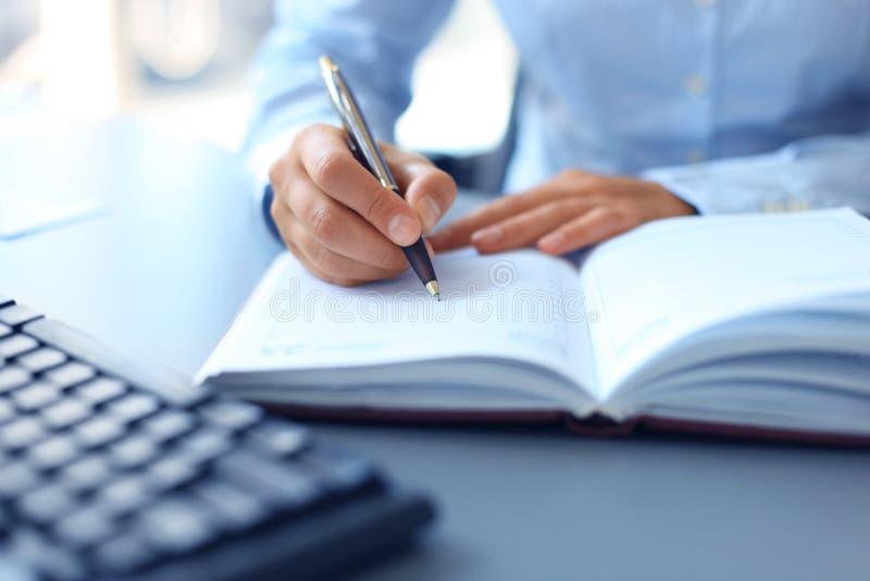 Geschäftsmann schreibt in ein Notizbuch lizenzfreie stockfotografie