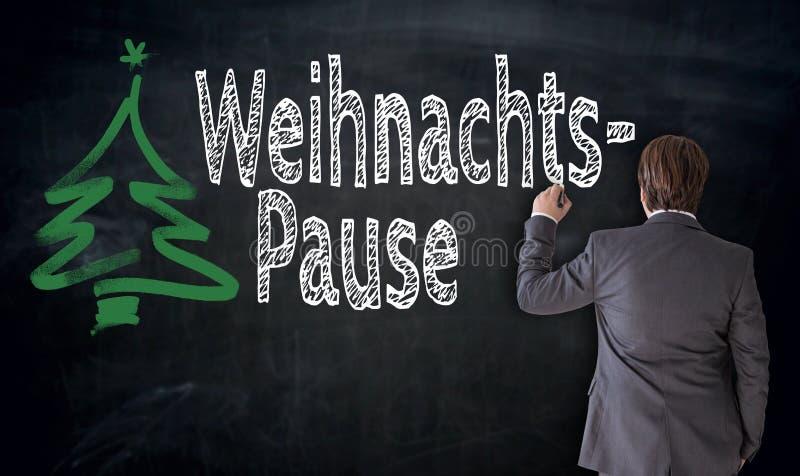 Geschäftsmann schreibt Weihnachtspause in deutsche Weihnachtspause O stockfoto