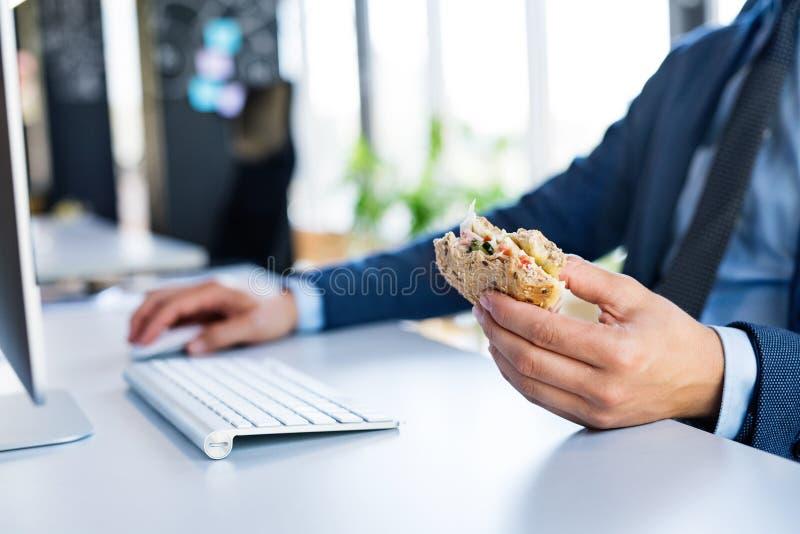 Geschäftsmann am Schreibtisch mit Computer das Mittagessen essend stockfoto