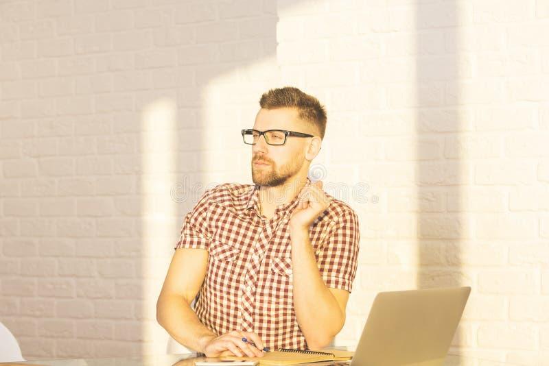 Geschäftsmann am Schreibtisch mit Laptop und Notizblock lizenzfreies stockbild