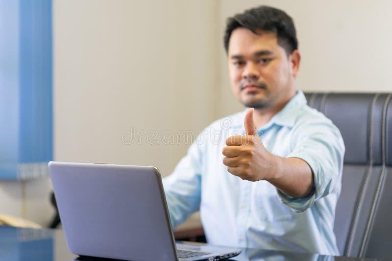 Geschäftsmann, Schreibtischarbeitskraft mit den Daumen des tragbaren Computers herauf showin stockfotografie