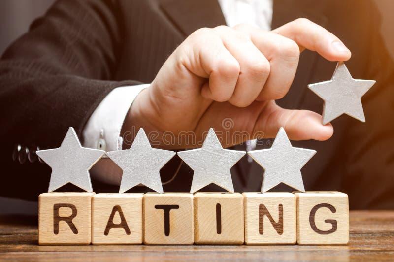 Geschäftsmann setzt den fünften Stern über der Wort Bewertung auf Holzklötze Das Konzept der hohen Bewertung der Hotels und der R lizenzfreie stockfotos