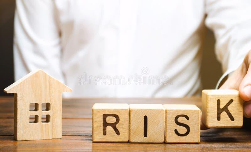 Geschäftsmann setzt Holzklötze mit dem Wort Risiko und einem Haus Immobilieninvestitionsrisiko Riskante Investitionen Vermögenssc lizenzfreie stockfotos