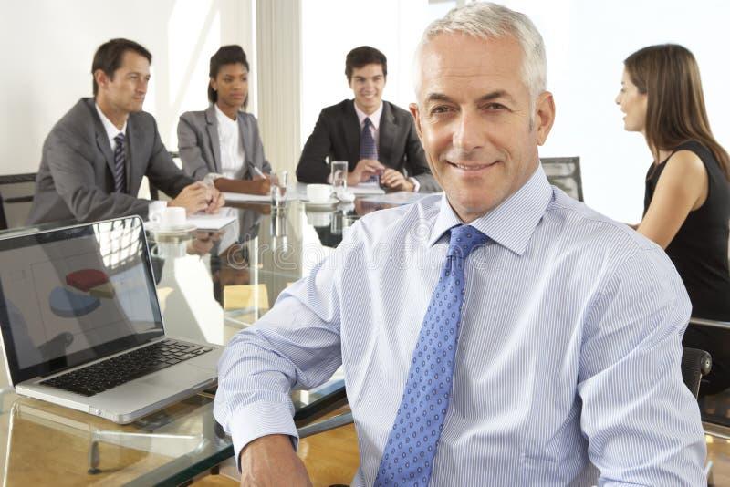 Geschäftsmann-Sitting Around Boardroom-Tabelle mit Kollegen stockbild