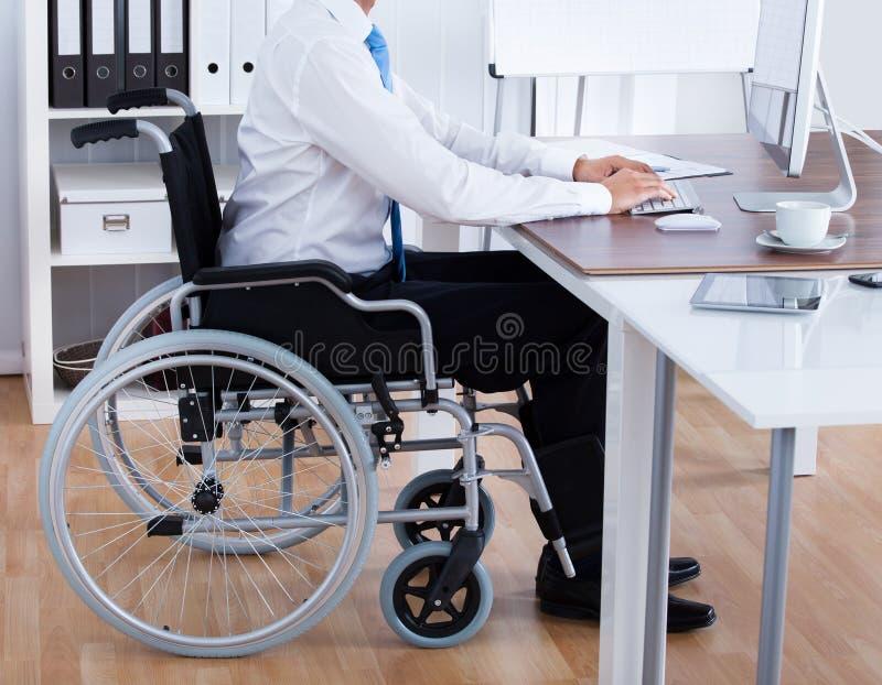 Geschäftsmann Sitting On Wheelchair und mit Computer stockfotos