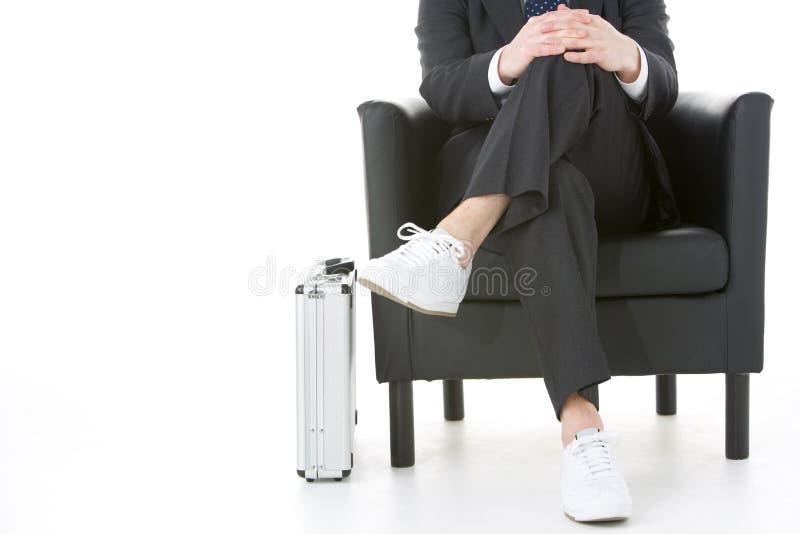 Geschäftsmann-sitzende tragende Turnschuhe stockfotografie
