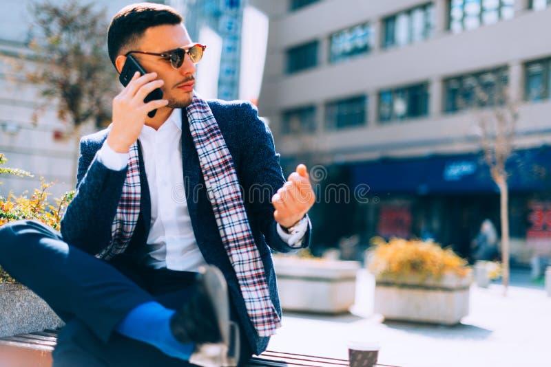 Geschäftsmann sitzt auf Bank im Stadtzentrum und im Unterhaltungso stockbilder