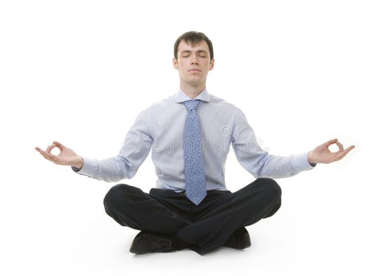 Geschäftsmann sitzt in Yogastellung stockbilder