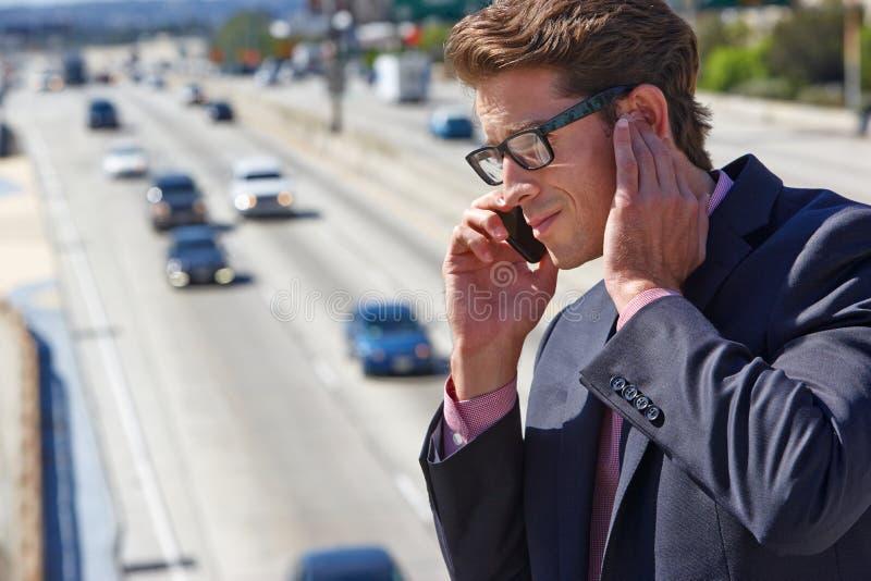 Geschäftsmann-Speaking On Mobile-Telefon durch laute Autobahn lizenzfreie stockbilder