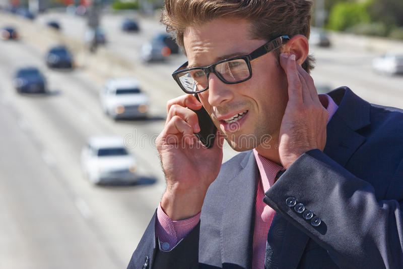 Geschäftsmann-Speaking On Mobile-Telefon durch laute Autobahn lizenzfreies stockbild