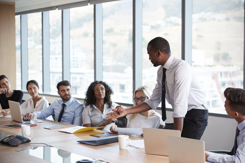 Geschäftsmann-Stands To Address-Sitzung um Brett-Tabelle stockbild