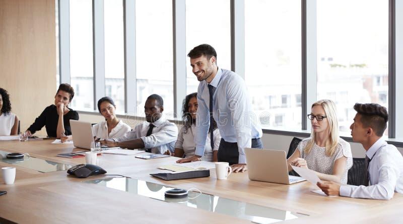 Geschäftsmann-Stands To Address-Sitzung um Brett-Tabelle stockfotos