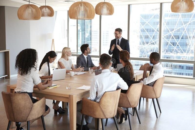 Geschäftsmann-Stands To Address-Sitzung um Brett-Tabelle lizenzfreie stockfotografie