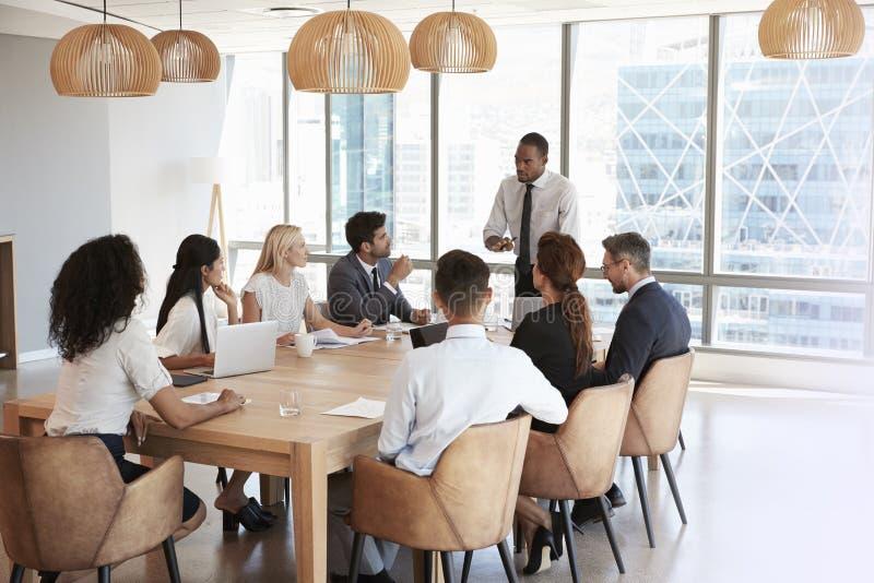 Geschäftsmann-Stands To Address-Sitzung um Brett-Tabelle stockbilder