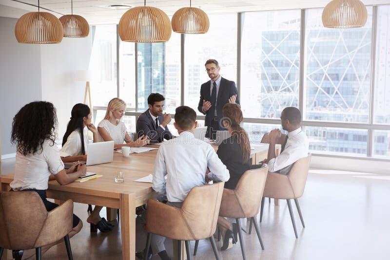 Geschäftsmann-Stands To Address-Sitzung um Brett-Tabelle stockfotografie