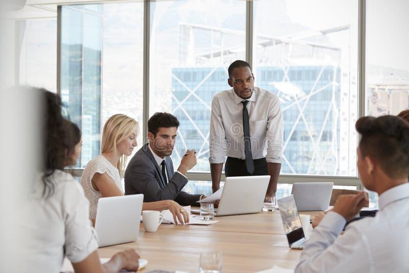 Geschäftsmann-Stands To Address-Sitzung um Brett-Tabelle lizenzfreie stockfotos
