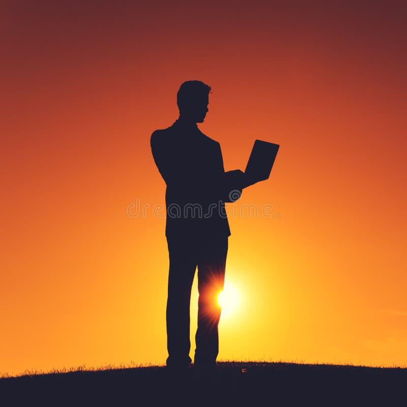 Geschäftsmann-stehender Hügel unter Verwendung des Laptop-Konzeptes lizenzfreie stockfotos