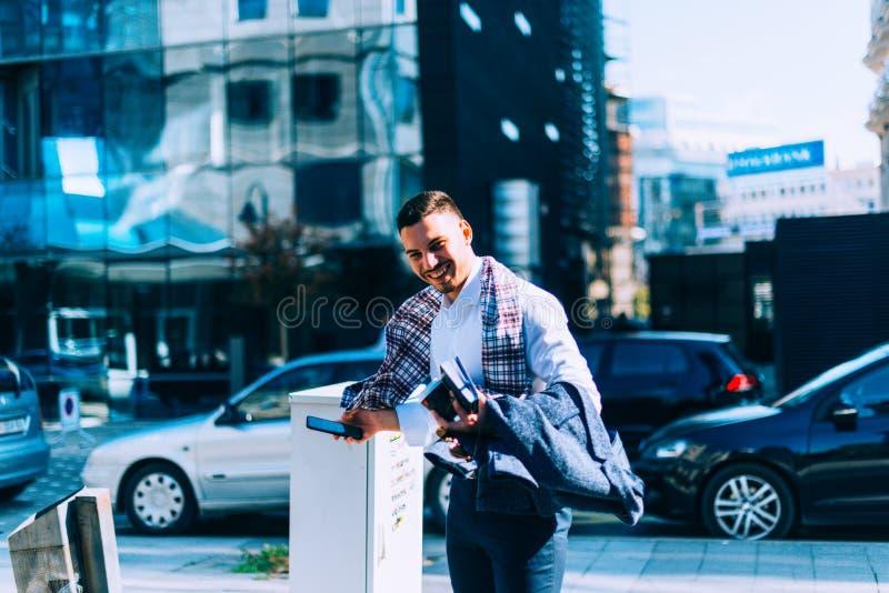 Geschäftsmann steht auf der Straße an einem windigen Tag und schaut interessiert lizenzfreies stockfoto