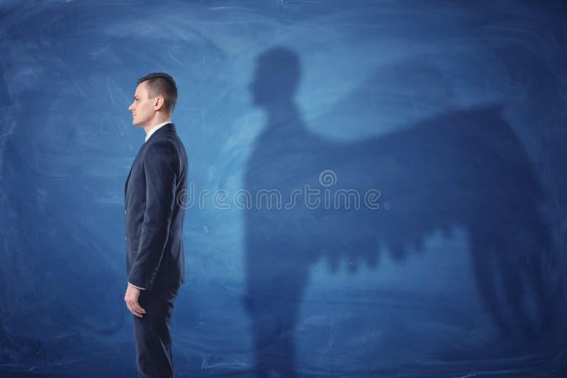 Geschäftsmann steht im Profil und wirft einen Schatten von Engelsflügeln auf blauem Tafelhintergrund lizenzfreies stockbild