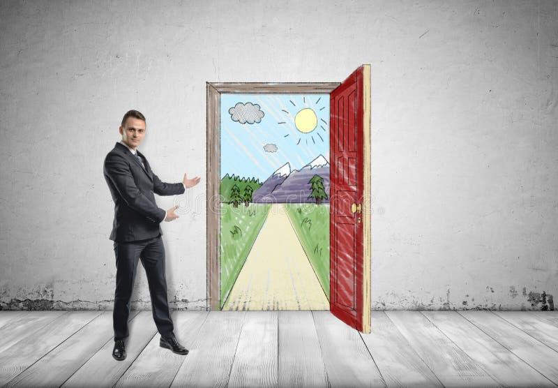 Geschäftsmann steht, zeigend sonnige Szene mit der Straße und den Bergen hinter einer offenen Tür durch beide Hände stockfotos