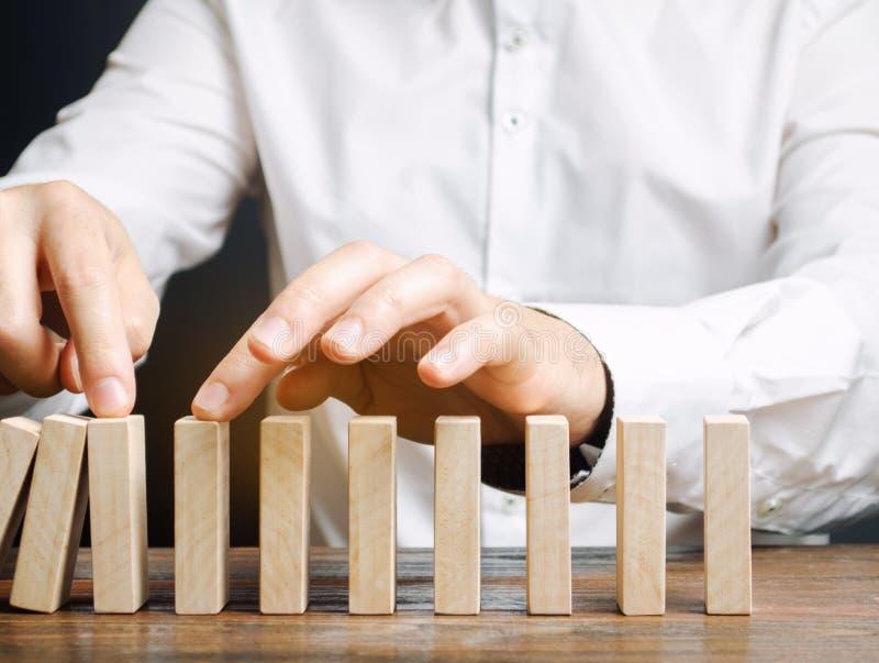 Geschäftsmann stoppt Einsturzdomino-effekt Druckwiderstandgeschäft Finanzstabilit?t Wiederaufnahmegeschäft Bewertung des Bargelde stockfoto