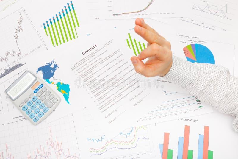 Geschäftsmann am Tisch mit den verschiedenen Finanzdaten, die das Zeichen - OKAY zeigen stockbilder