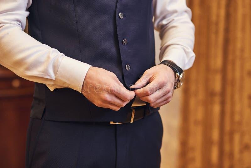 Geschäftsmann trägt eine Jacke, Manneshände Nahaufnahme, der Bräutigam, der morgens vor Hochzeitszeremonie fertig wird lizenzfreie stockfotos