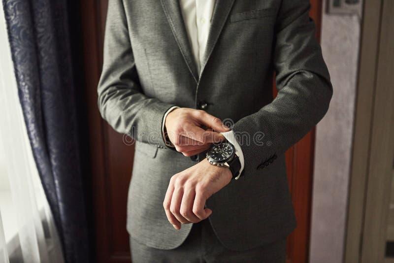 Geschäftsmann trägt eine Jacke, Manneshände Nahaufnahme, der Bräutigam, der morgens vor Hochzeitszeremonie fertig wird stockfotografie