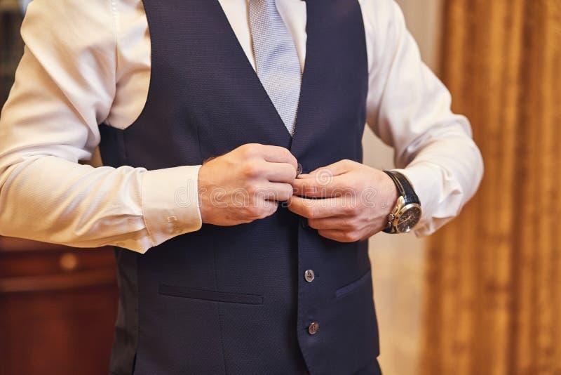 Geschäftsmann trägt eine Jacke, Manneshände Nahaufnahme, der Bräutigam, der morgens vor Hochzeitszeremonie fertig wird Mannmode lizenzfreie stockfotos