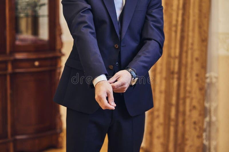 Geschäftsmann trägt eine Jacke, Manneshände Nahaufnahme, der Bräutigam, der morgens vor Hochzeitszeremonie fertig wird Mannmode stockbilder