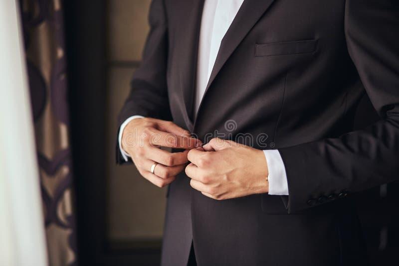 Geschäftsmann trägt eine Jacke, Manneshände Nahaufnahme, der Bräutigam, der morgens vor Hochzeitszeremonie fertig wird Mannmode lizenzfreie stockbilder