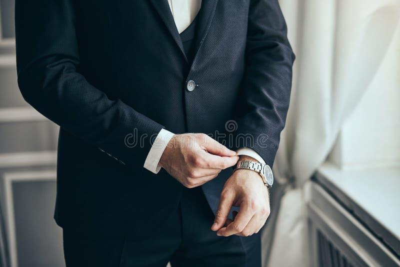 Geschäftsmann trägt eine Jacke, Manneshände Nahaufnahme, der Bräutigam, der morgens vor Hochzeitszeremonie fertig wird Mannmode stockfotografie