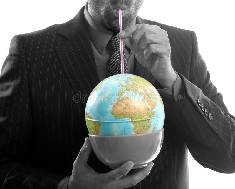 Geschäftsmann trinkt Welt, Leistungführermetapher lizenzfreie stockbilder