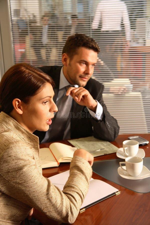 Geschäftsmann und Frau, die in der Büroumgebung sprechen lizenzfreies stockbild