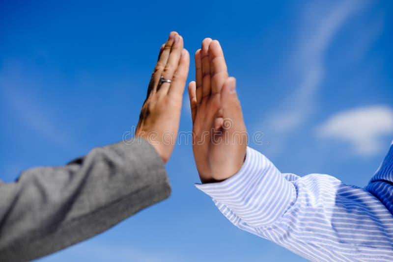 Geschäftsmann und Frau, die fünf, nahe hohe Hände geben stockbilder