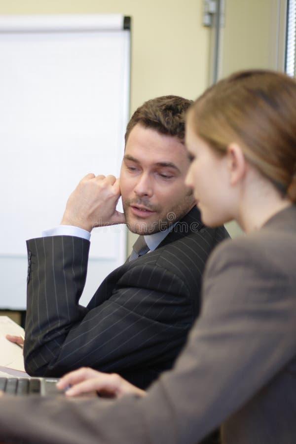 Geschäftsmann und Frau, die im Büro sprechen stockfoto