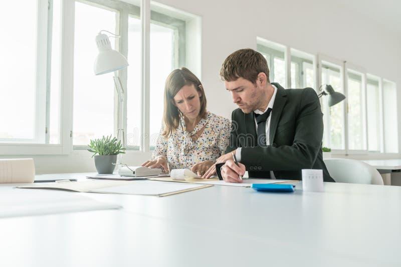 Geschäftsmann und Frau, die manuelle Buchhaltung tun lizenzfreie stockbilder