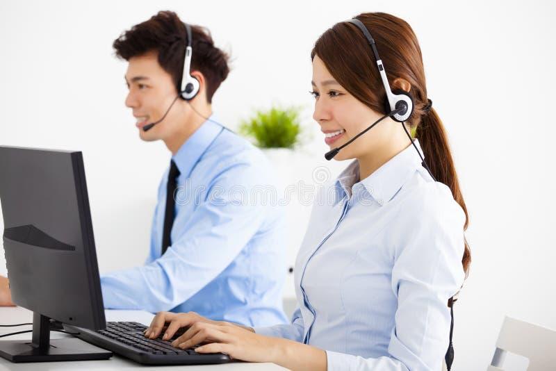 Geschäftsmann und Frau mit dem Kopfhörer, der im Büro arbeitet lizenzfreie stockfotografie