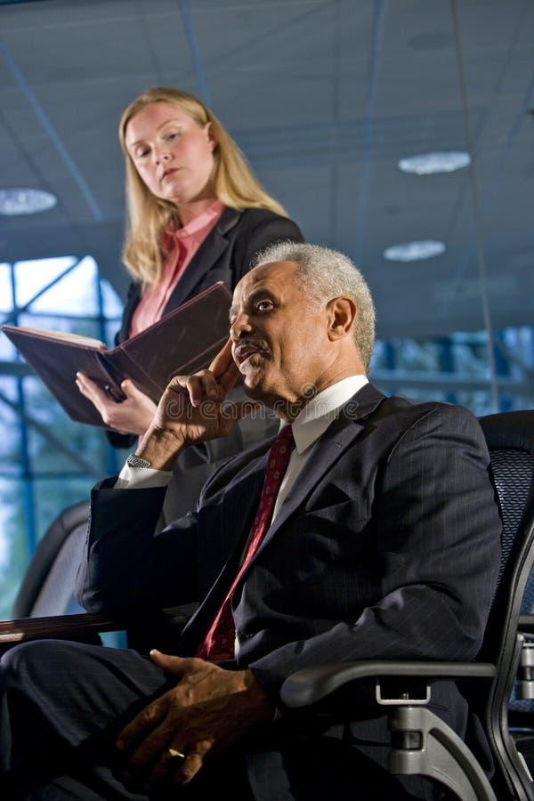 Geschäftsmann- und Frauassistent im Sitzungssaal stockfotografie