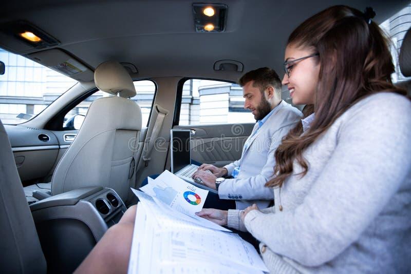 Geschäftsmann und Geschäftsfrau, die Diagramme und Diagramme kontrollieren stockfotos