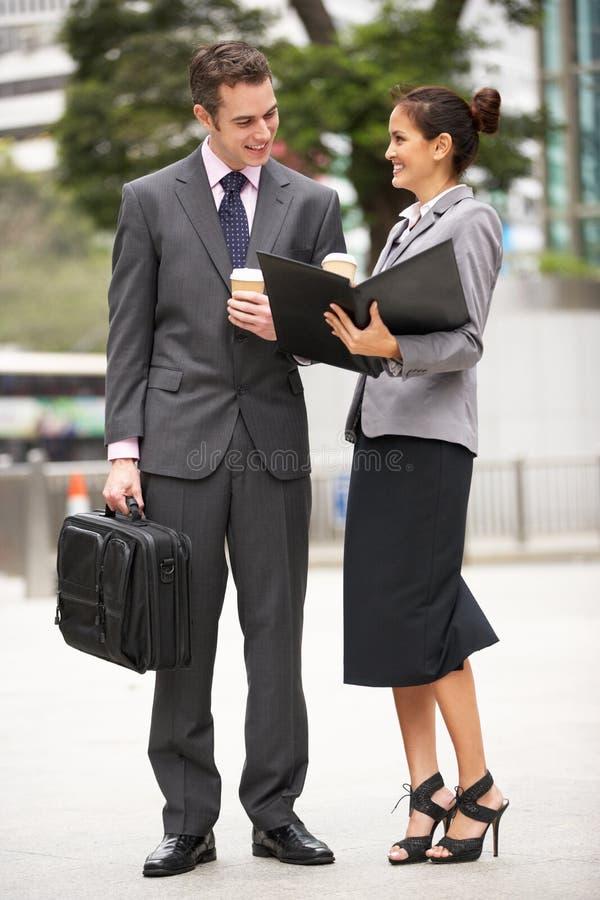 Geschäftsmann und Geschäftsfrau, die Dokument behandeln stockbild