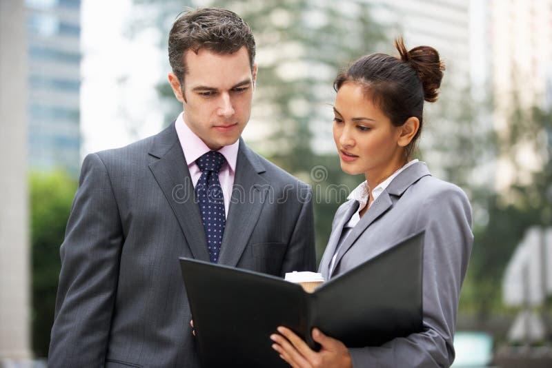 Geschäftsmann und Geschäftsfrau, die Dokument behandeln stockfotografie