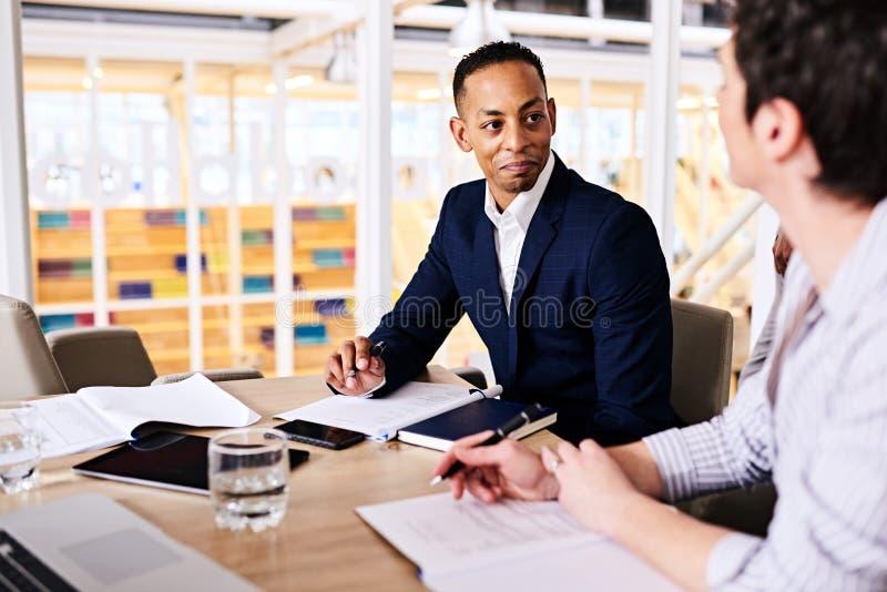 Geschäftsmann und Geschäftsfrau, die kooperatives Geschäft in der Chefetage dicussing sind stockfotografie