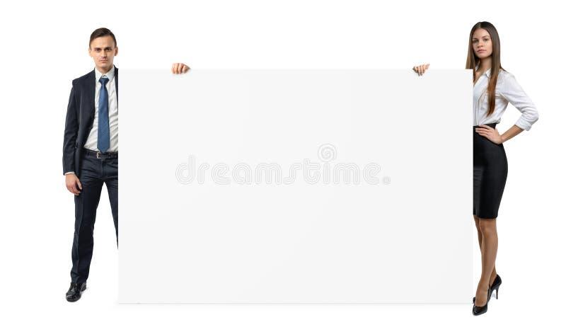 Geschäftsmann und Geschäftsfrau halten beide Seiten einer leeren Fahne, die auf weißem Hintergrund lokalisiert wird stockfotografie