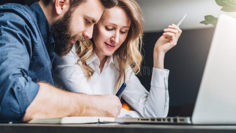 Geschäftsmann und Geschäftsfrau sitzen bei Tisch vor dem Laptop und besprechen Geschäftskonzept Mann schreibt Stift stockfoto